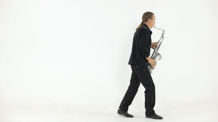 Man in dark shirt and trousers playing the saxophone