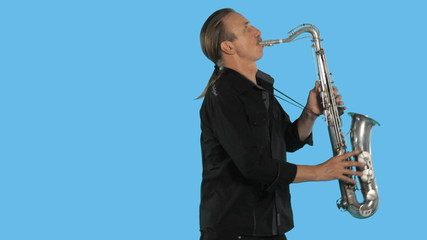 Saxophonist in black shirt playing the saxophone in the studio
