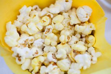 Tasty popcorn in yellow paper bag