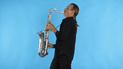 The man in black shirt playing the saxophone
