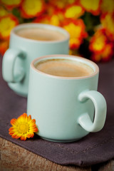 Cup of coffee with bright autumn flowers