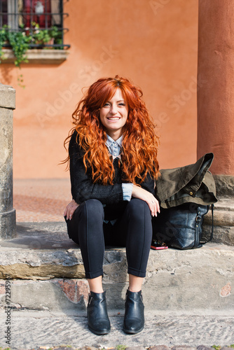 Smiling redhead woman portrait sit outdoors in the street.