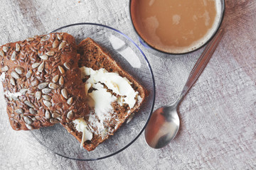 grain rye bread and butter and cup of coffee