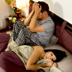 Sad couple after fight in bed