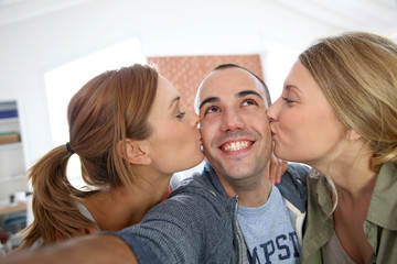 Cheerful guy taking picture of girls kissing him