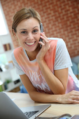Smiling girl at home talking on mobile phone