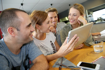 Group of friends in campus lounge websurfing with tablet