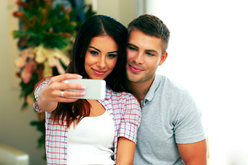 Happy couple making selfie photo with smarphone