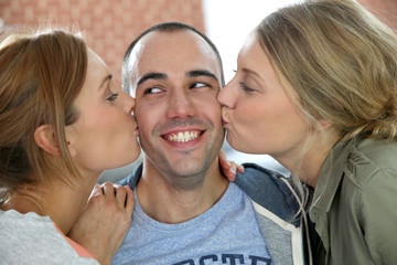 Lucky guy being kissed by 2 girl friends