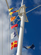 Nautical Flags Hanging from a Ship's Mast with Wispy Clouds - 72298793
