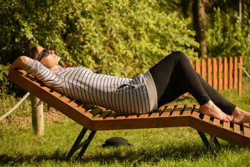 Side profile of a young women resting on lounge chairs outdoors