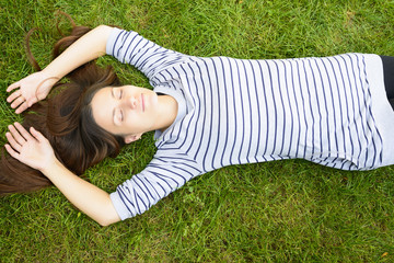 Young woman laying down on green grass with eyes closed