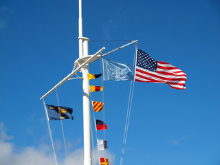 Nautical and American Flags Hanging from a Ship's Mast with Wisp