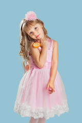 Little girl posing in a studio over colour background. Holding a