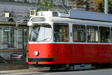red tram carries passengers for European cities