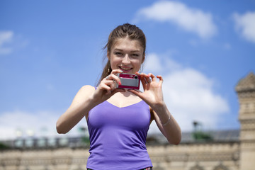Young happy woman taking pictures on your camera