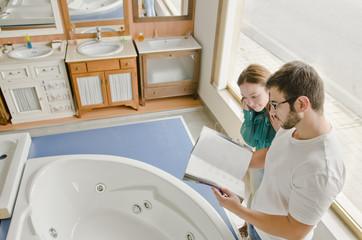 Hmbre y mujer observan catalogo en tienda de muebles