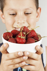 Boy holding plate with strawberry
