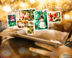 Young woman viewing christmas photos by using digital tablet