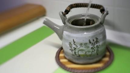 Acqua calda versata in teiera con tè verde