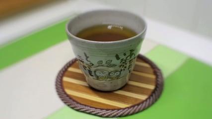 Una mano mette una tazza di tè su tavolo