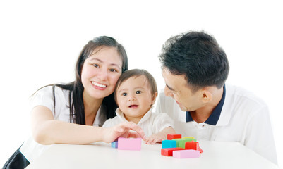 Asian cute baby playing toys accompanied by parents