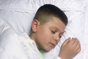 Cute boy asleep on white cushion