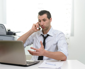 Businessman with laptop talkng on the phone