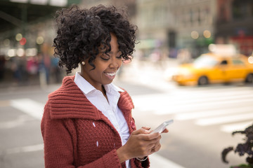 African American black woman in city texting cellphone