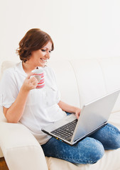 Woman using laptop and drinking from a mug on the sofa