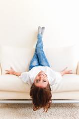 Woman lying upside down on a sofa