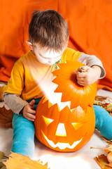 A cute photograph of a boy and her lighting Halloween pumpkin