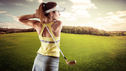 Young female in sportswear playing golf on green field