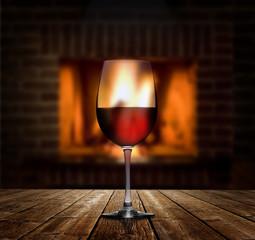 Rotweinglas vor Kaminfeuer