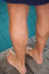 Close up low section of swimmer standing by pool
