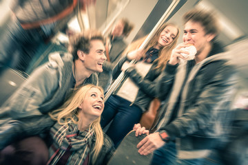 Group of young hipster friends talking in subway train
