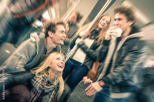 Leinwanddruck Bild Group of young hipster friends talking in subway train