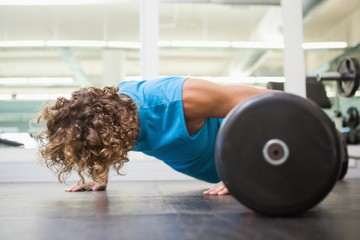 Side view of young man doing push ups in gym