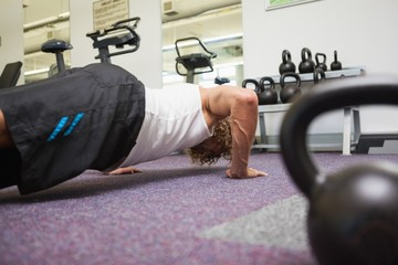 Side view of man doing push ups in gym