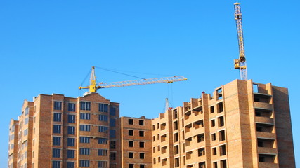 timelapse of three construction cranes building new brick house
