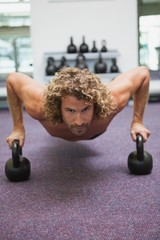 Handsome man doing push ups with kettle bells in gym
