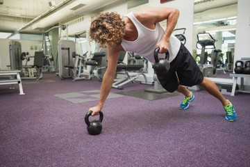 Side view of man exercising with kettle bells in gym