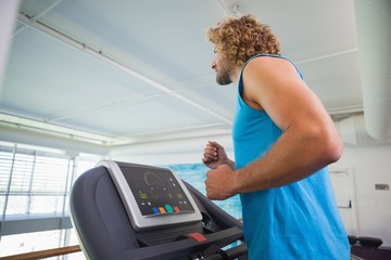 Side view of man running on treadmill in gym