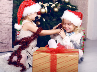 cute little girls having fun beside a Christmas tree