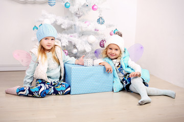 funny little girls posing beside a decorated Christmas tree
