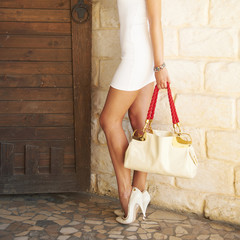 Female shod white high heel shoes holding in a hand fashion bag.