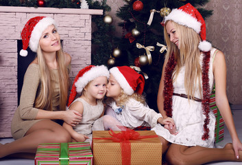 happy family posing beside a decorated Christmas tree