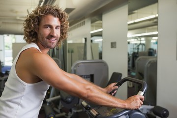 Side view portrait of man working out on exercise bike