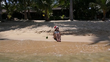 Young Woman on the Beach in Santa's Hat on Christmas