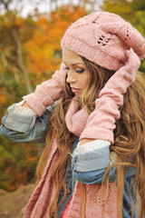 Woman dressed in pink knitted hat and glovesn park.